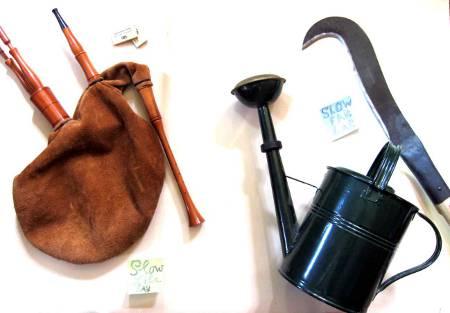 Hintergrundbild mit Hummel (Dudelsack), Kultursense und Gießkanne aus Metall