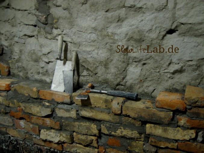Sandsteinmauer mit Kellen und Hammer davor